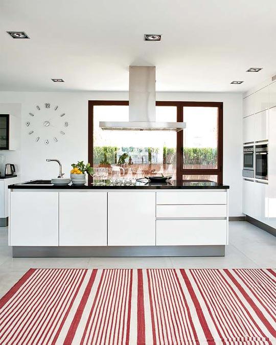 Cocina muy luminosa de muebles blancos y grandes ventanales.