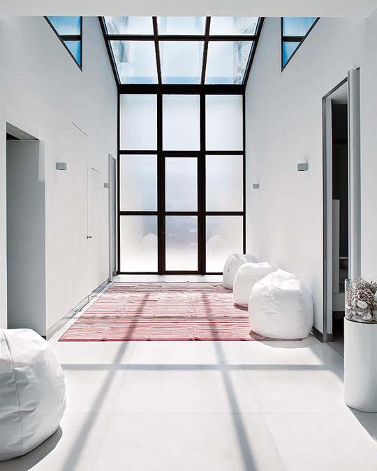 Hall de entrada con puerta integrada en una cristalera.