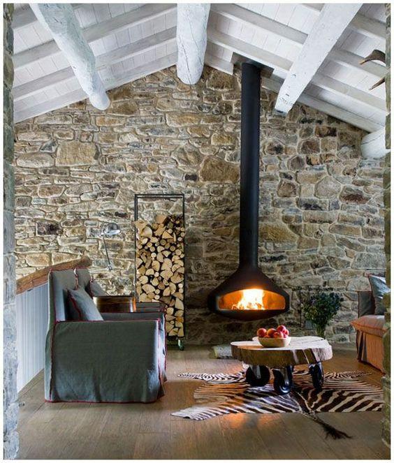 Salones con pared de piedra y chimenea